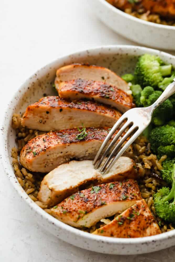Baked chicken cut up with broccoli in a bowl over brown rice.