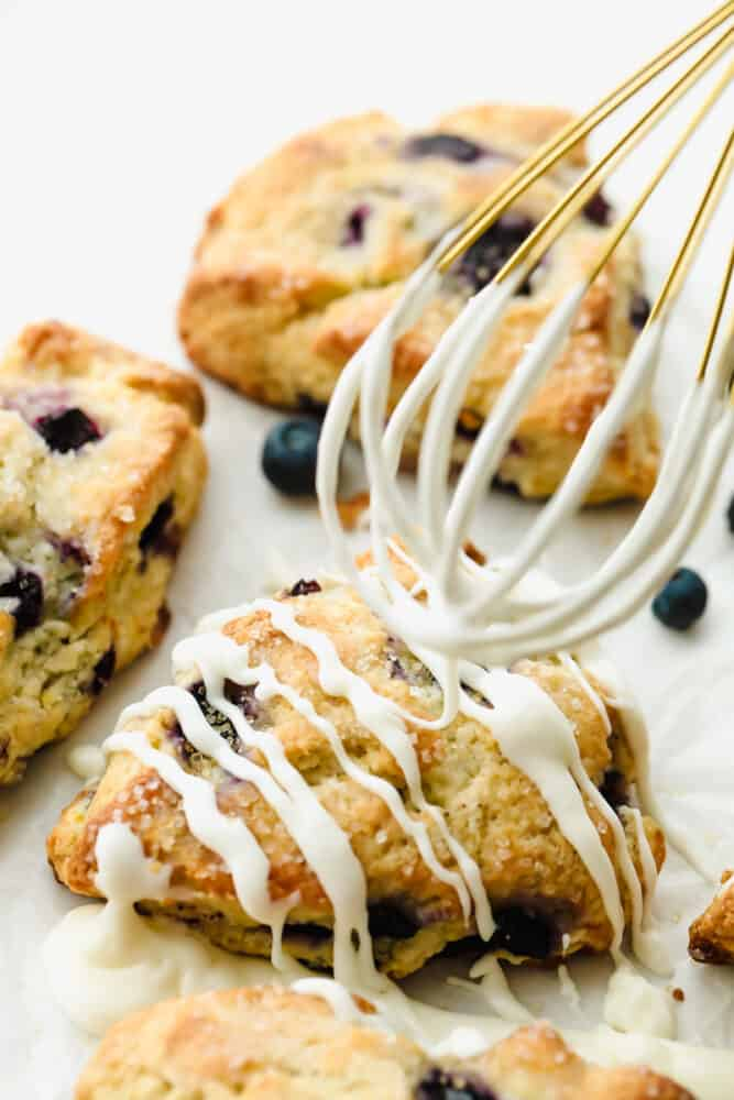 Drizzling icing on top of Blueberry Scones.
