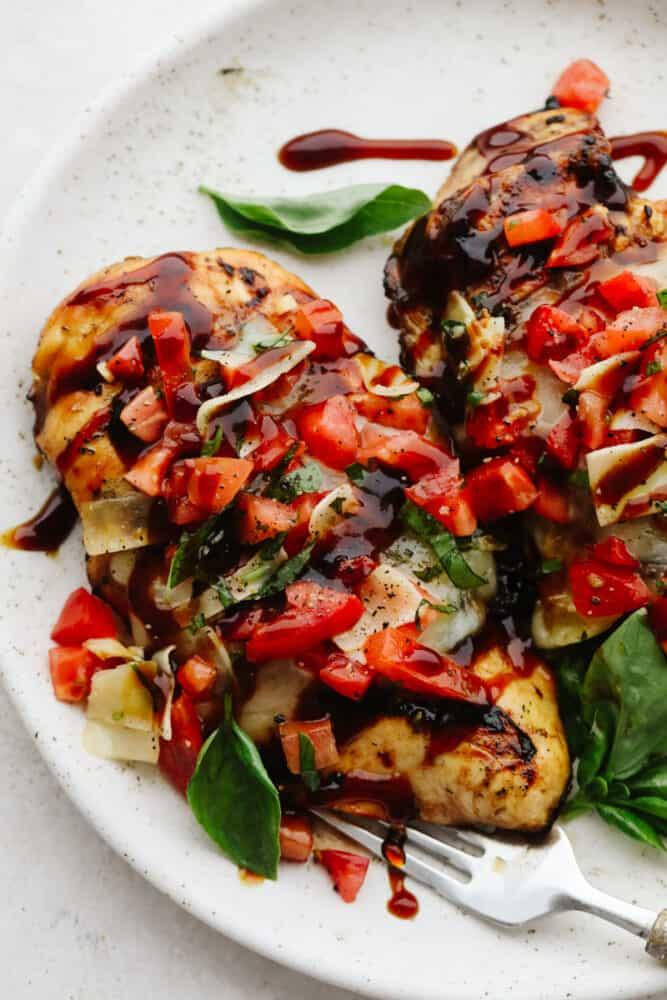 Bruschetta chicken on a white plate.