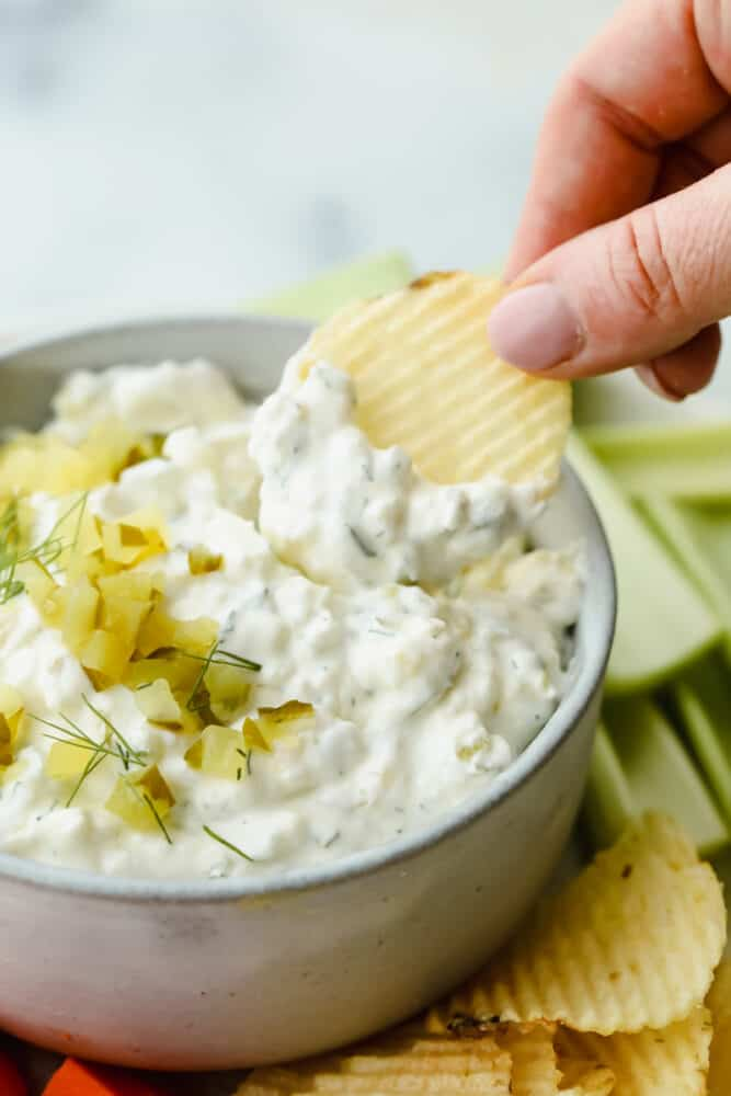 Putting dill pickle dip on a potato chip.