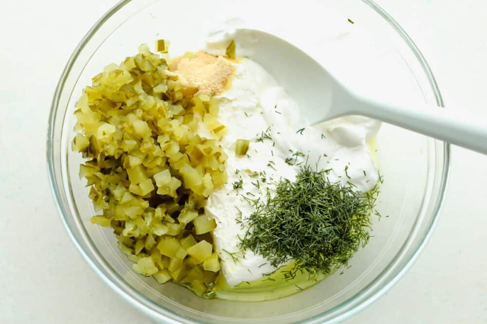 Dill pickle dip ingredients in a glass bowl.