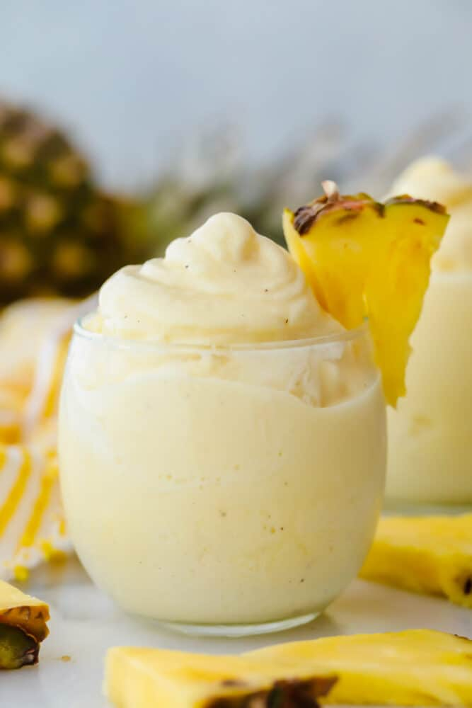 Dole pineapple whip in a glass with fresh pineapple garnish.