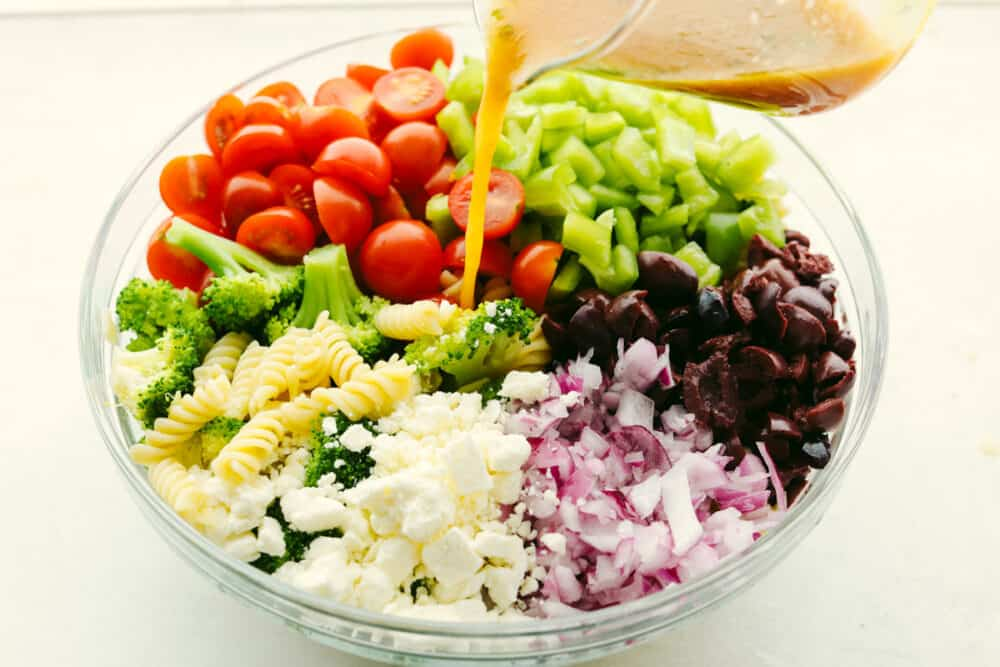 Pouring dressing over pasta salad.