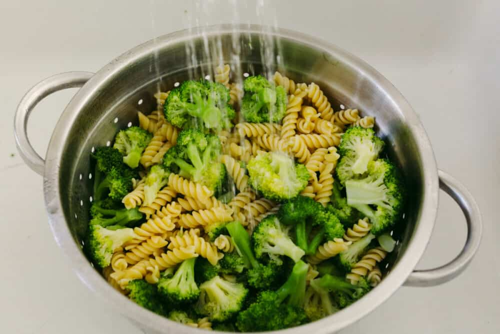 Straining veggies and pasta and rinsing with cold water.