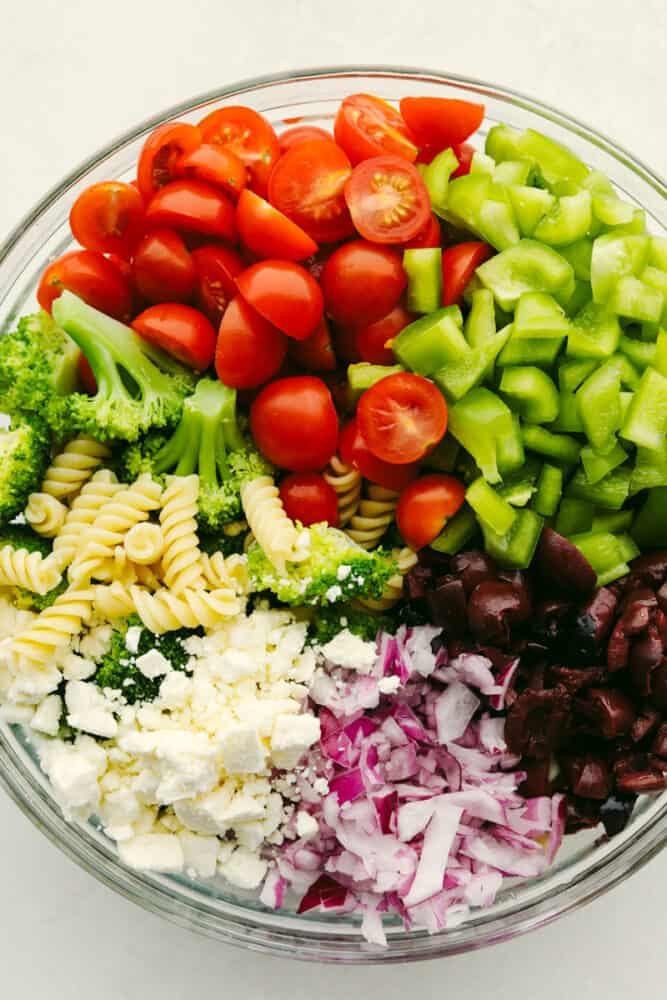 A variety of vegetables and cheese in a bowl, ready to be mixed.