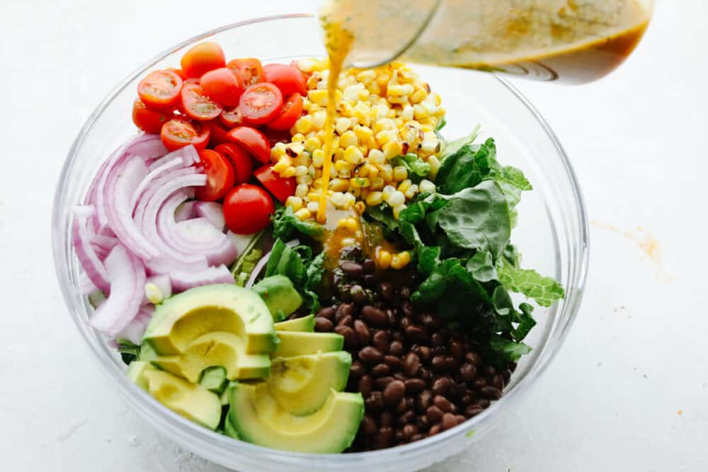 Pouring chipotle dressing over vegetbles.