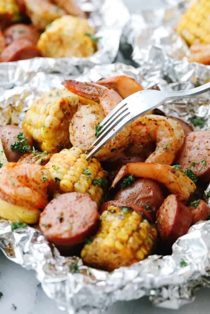 Taking a bite of corn in a Shrimp Boil Foil Packet.