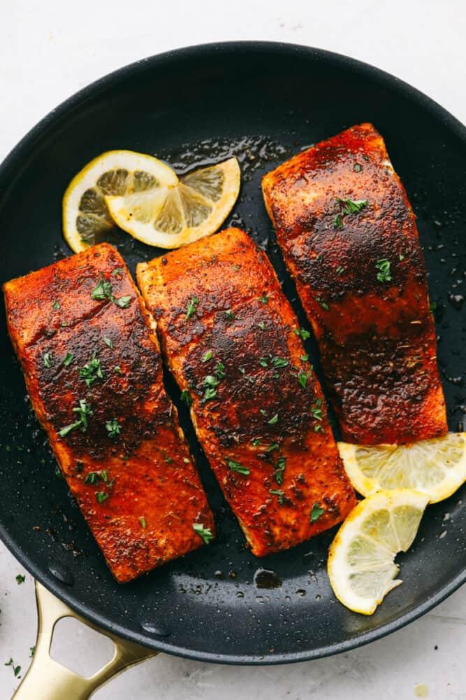 Slices of lemon garnish fillets of blackened salmon.