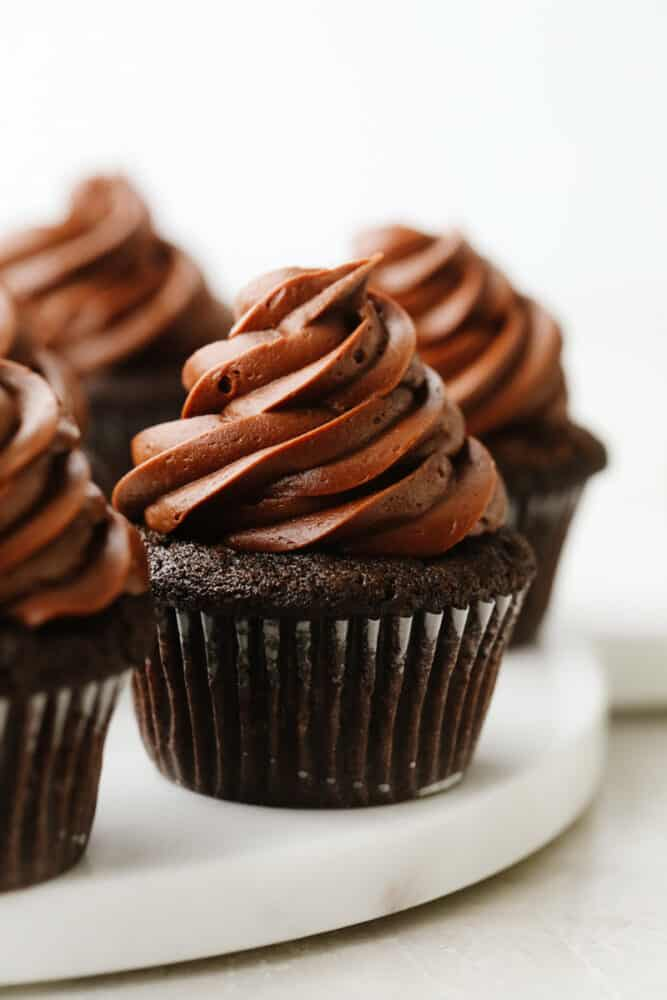 Frosted chocolate cupcakes on a serving dish.