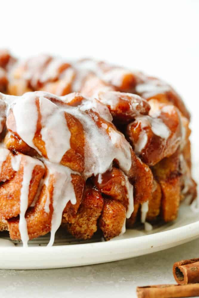 Finished cinnamon roll monkey bread on a white serving dish.