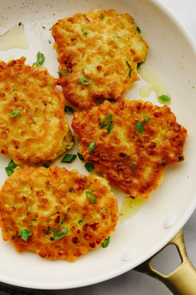Corn fritters on a plate garnished with green onions.