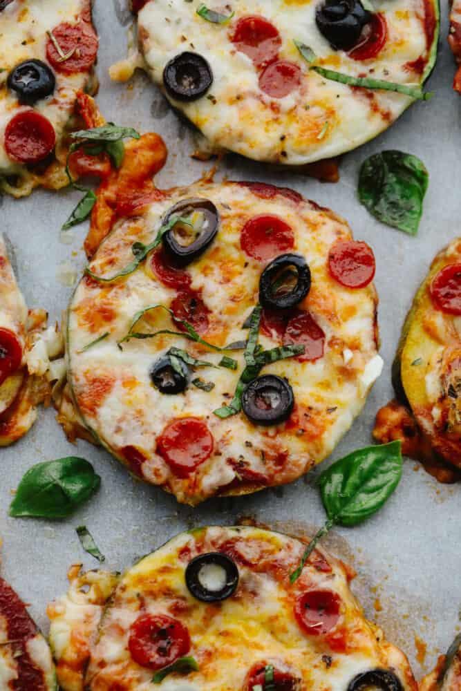 Close-up of zucchini pizza bites with basil garnish.
