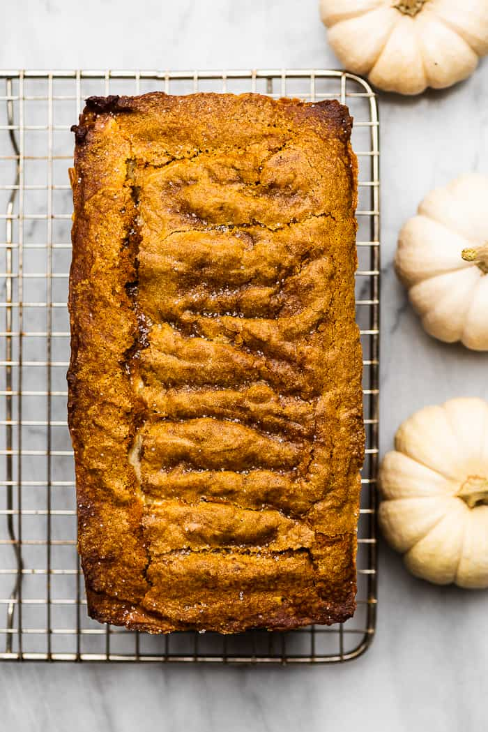 cream cheese pumpkin loaf on a cooling rack surrounded by white pumpkins.