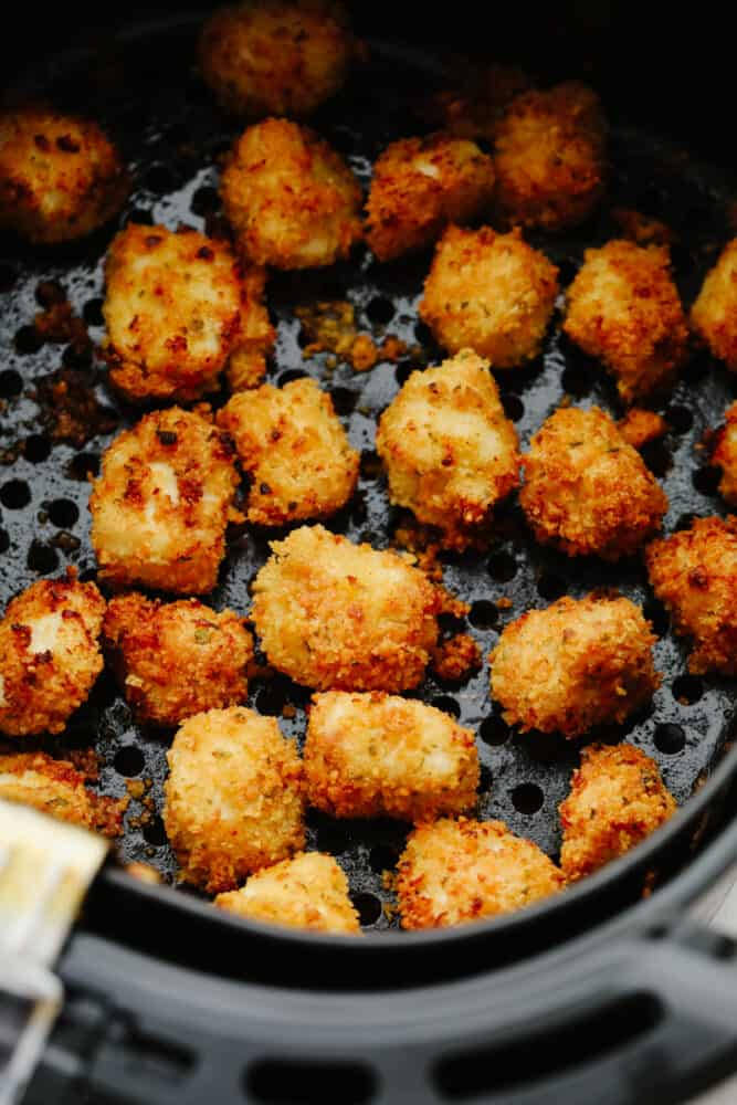 Chicken nuggets cooking in an air fryer.