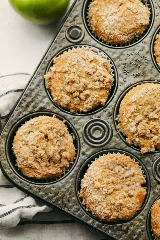 Apple streusel muffins in a muffin tin.