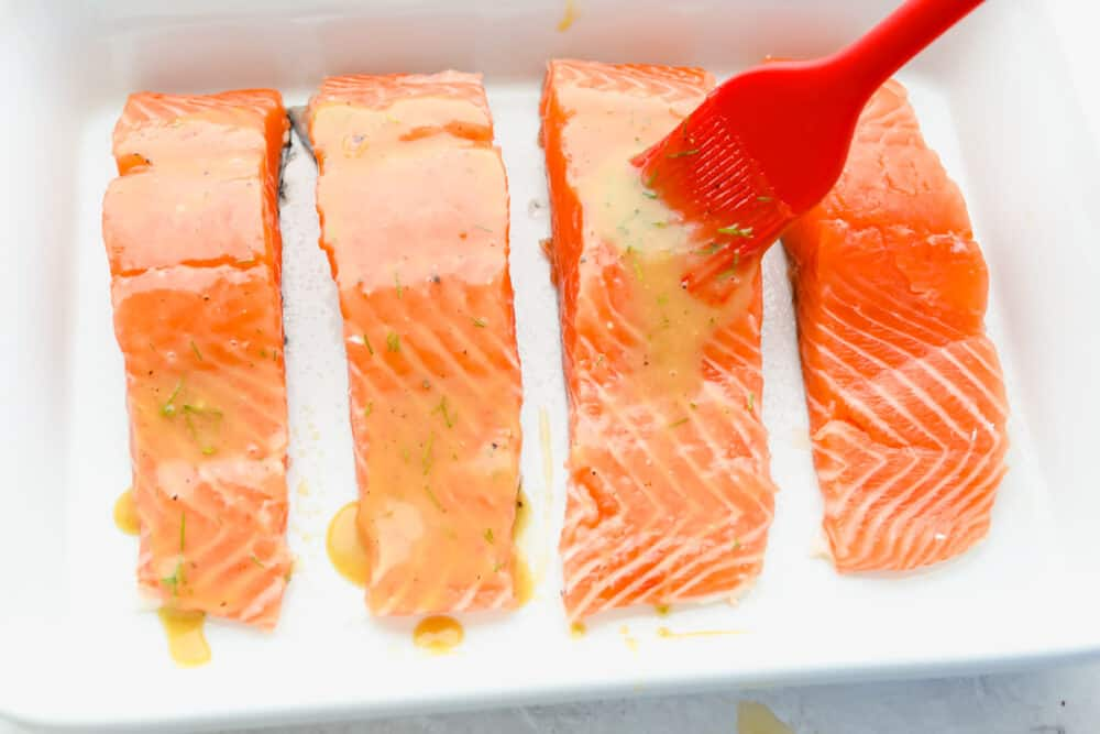Salmon filets being basted before being cooked.