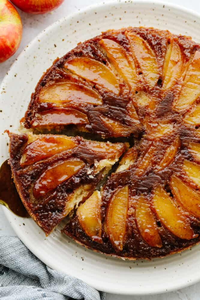 Taking a slice out of caramel apple upside down cake, served on a white dish.