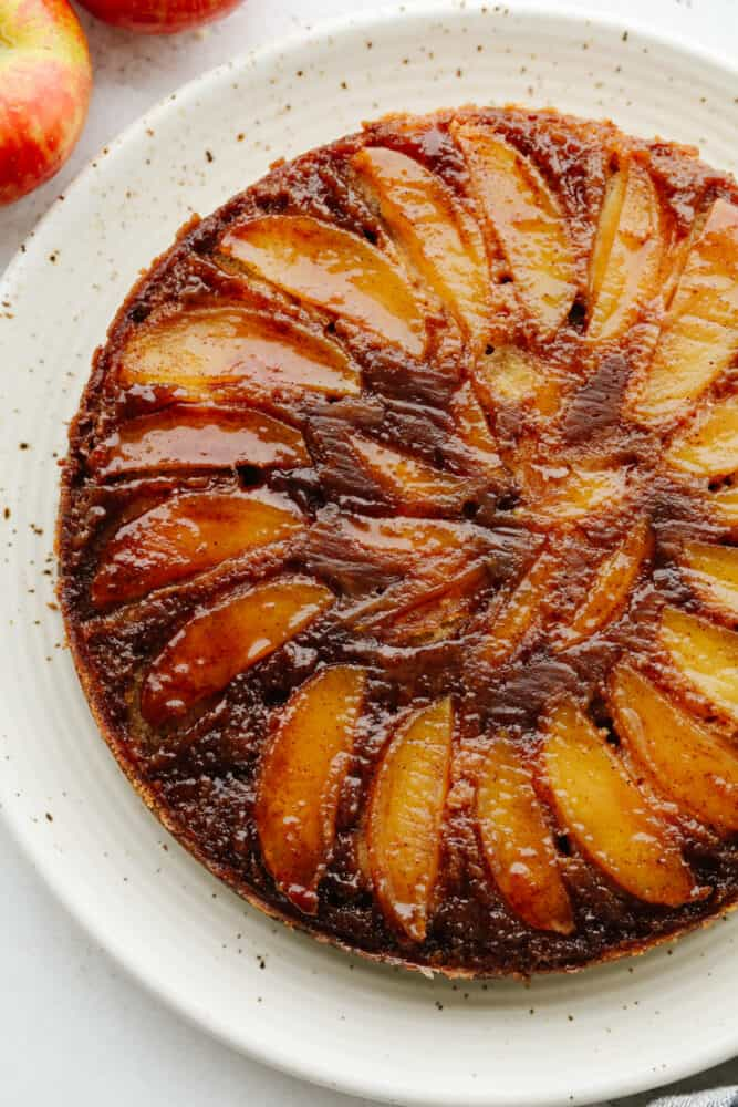 A full caramel apple upside-down cake on a white serving dish.