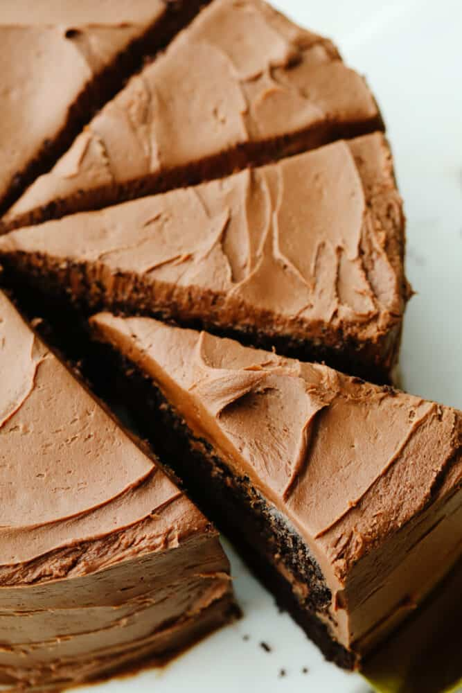 A whole chocolate cake that has been sliced.