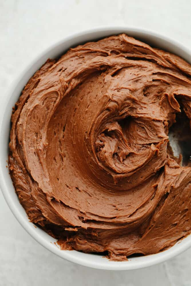 A white bowl filled with chocolate cream cheese frosting.