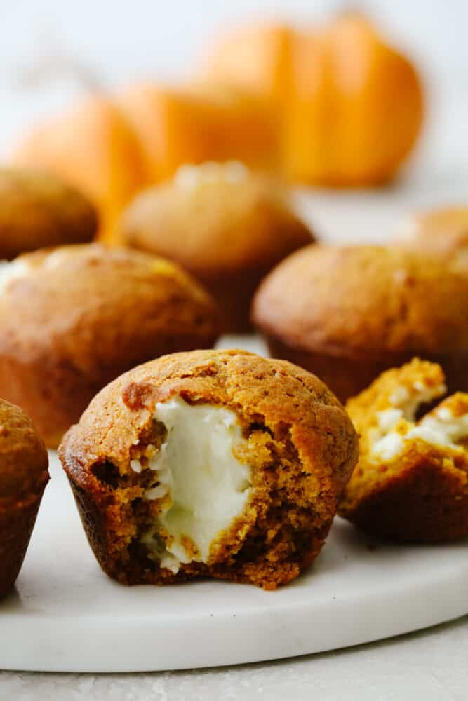 Pumpkin muffin cut in half showing cream cheese in the middle.