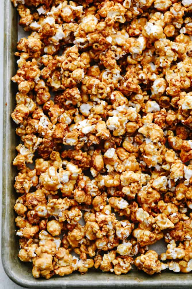 Caramel corn on a baking sheet that is cooked and crunchy.