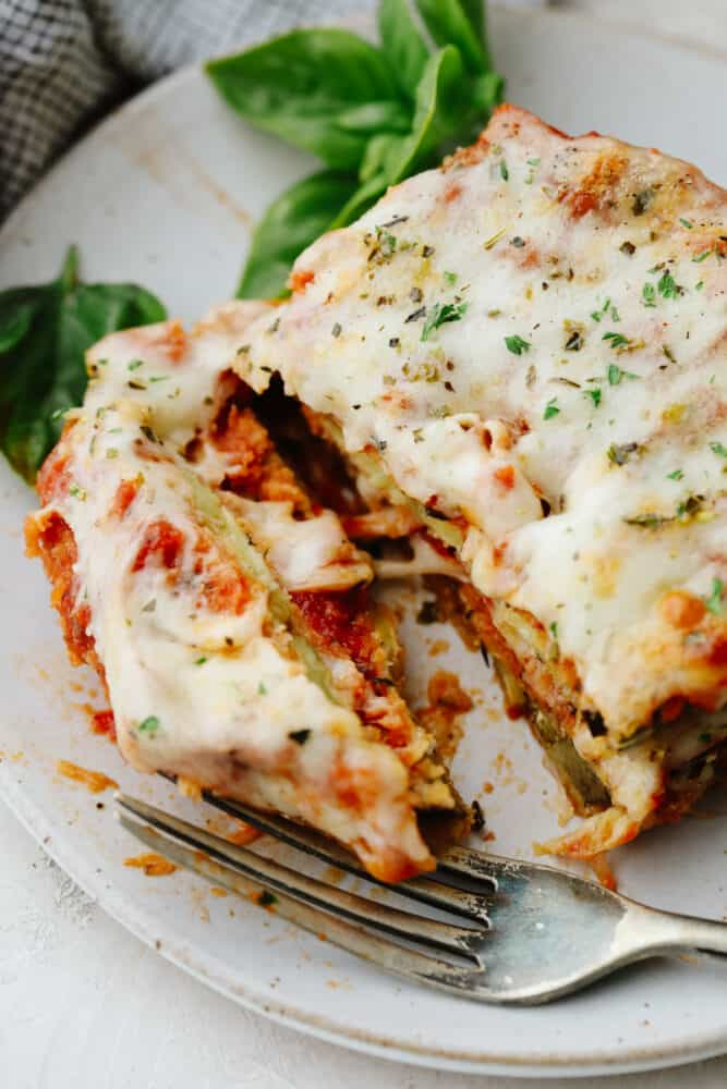 Eggplant parmesan being cut into with a fork.