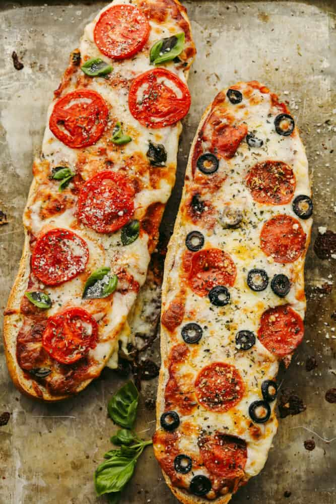 2 loaves of French bread pizza with different toppings.