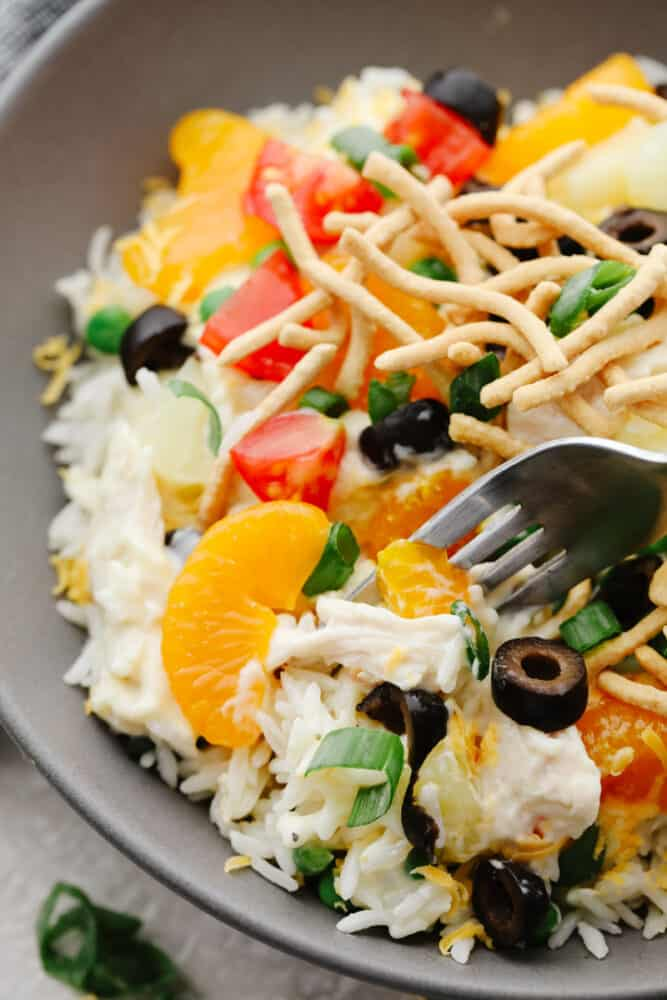 A closeup of a Hawaiian haystack with olives, mandarin oranges, tomatoes, and chow mein noodles as toppings.