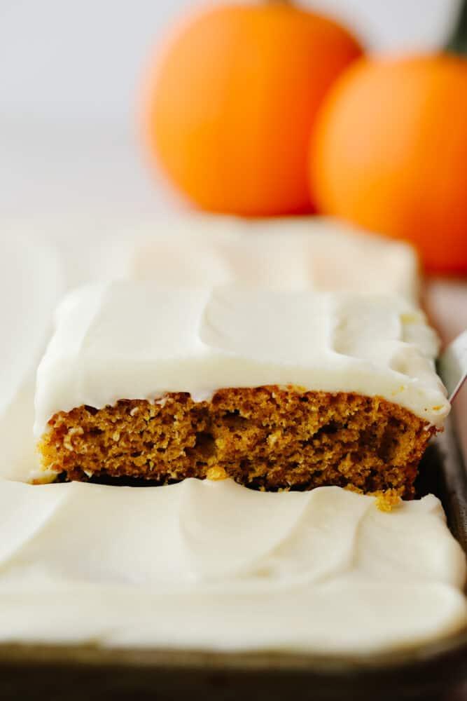 Pumpkin spice sheet cake being served from a baking sheet.