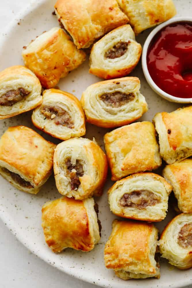 Sausage rolls on a platter with ketchup.