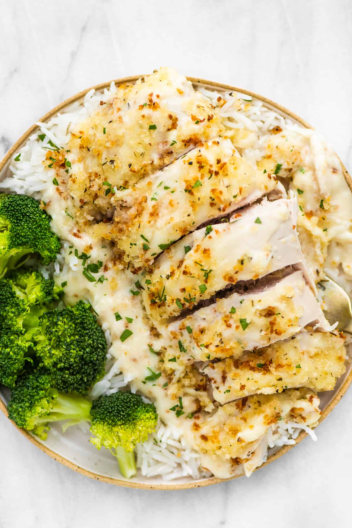 Swiss chicken bake on a plate with rice and broccoli.
