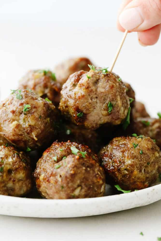 A stack of meatballs with someone putting a toothpick in one of them.