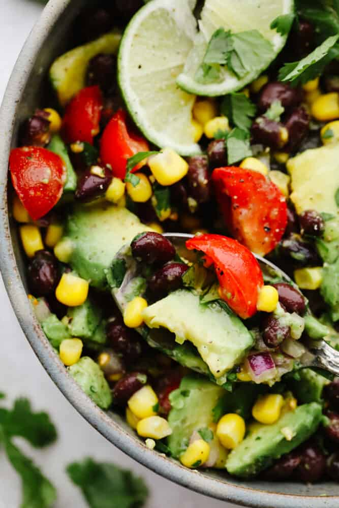 Black bean and corn salad on a spoon.