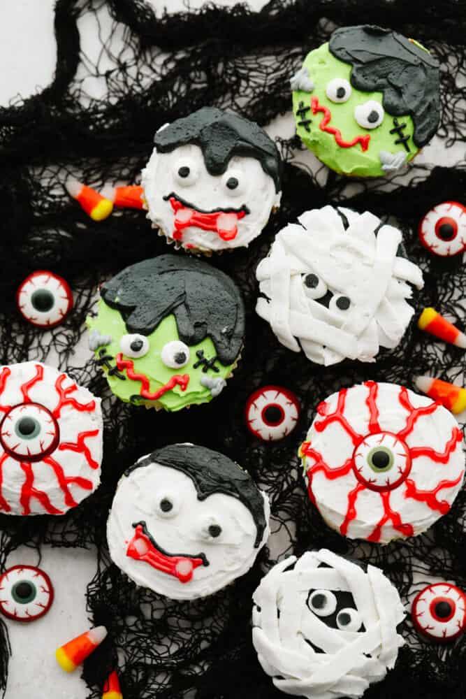 Various Halloween cupcakes served on black netting.