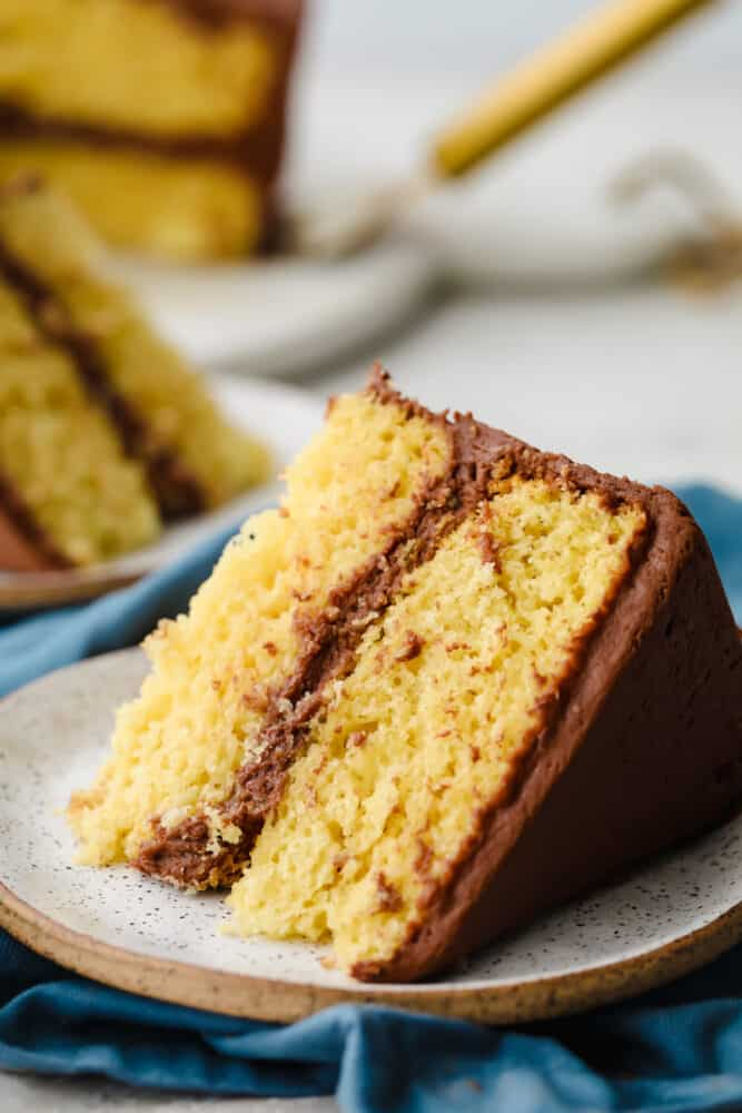 A slice of yellow cake with chocolate frosting.